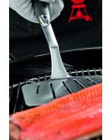 Spatola Weber da pesce in inox mentre gira del salmone su placca di cedro